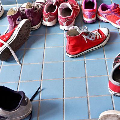 Kenkiä koulun lattialla.