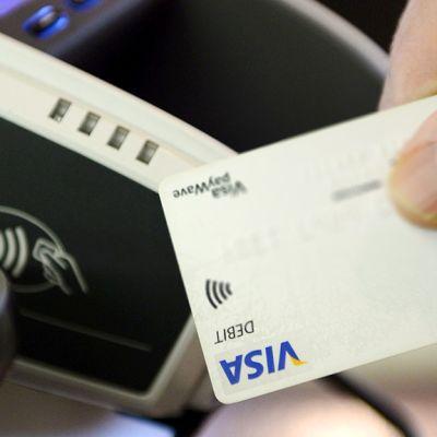 Henkilö maksaa Visa electron -kortilla.