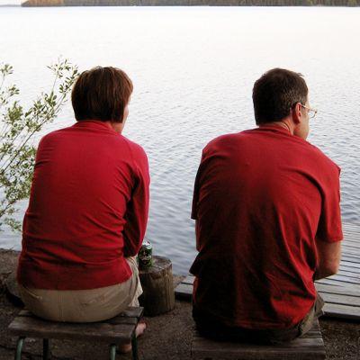 Nainen ja mies istuvat järven rannalla.