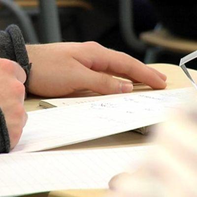 Opiskelija kirjoittaa muistiinpanoja.