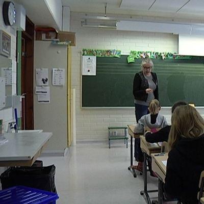 Opettaja puhuu luokalle.