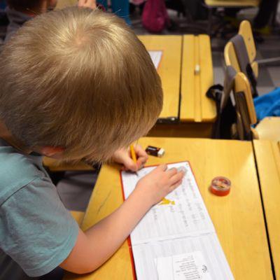 Alakoululainen kirjoittaa pulpetissaan vihkoon.