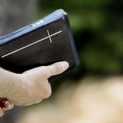 Pappi kädessään raamattu.