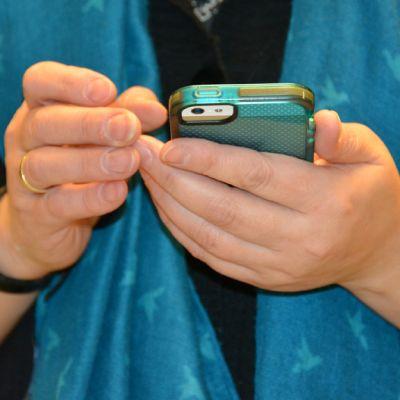 Kuvassa naisella on käsissään kännykkä