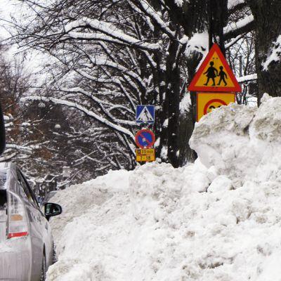 Korkea lumikasa tien reunassa.