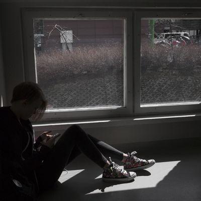 Nuori katsoo kännykkäänsä ikkunan edustalla.