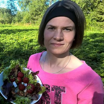 Nainen seisoo mansikkapellolla salaattikulho kädessä.