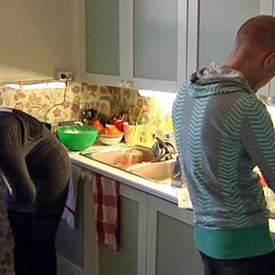 mies ja nainen laittavat ruokaa keittiössä