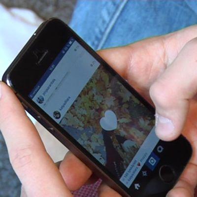 Nuori selaa älypuhelimella Instagramia.