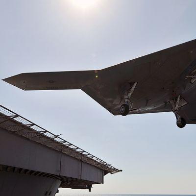 Yhdysvaltain laivaston miehittämätön lennokki laskeutuu lentotukialuksen kannelle.