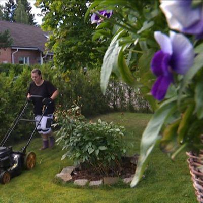 Nainen leikkaa nurmikkoa