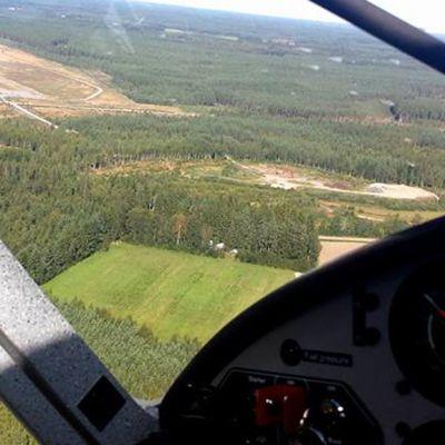 Kuvassa näkymä lentokoneen ohjaamosta maahan. Metsää, peltoja ja ohjaamon mittareita.