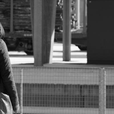 Tuntematon henkilö kuvattuna rautatieasemalla selkäpuolelta.