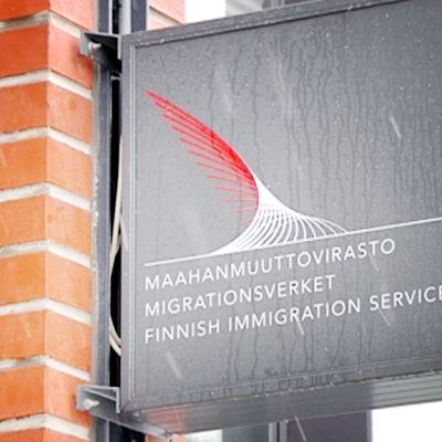Maahanmuuttoviraston kyltti lumisateessa.