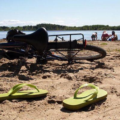 Polkupyörä ja varvassandaalit hiekkarannalla.