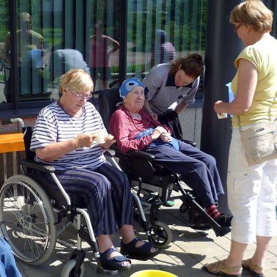 Vanhuksia pyörätuleissa auringonpaisteessa.