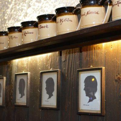 Kanta-asiakkaiden tuoppeja ja silhuettikuvia Ohranjyvän seinällä.