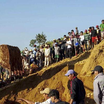 Ison kuopan laidoile kertyneet ihmiset seuraavat, miten kaivinkone kaivaa maata ruumiiden löytämiseksi.