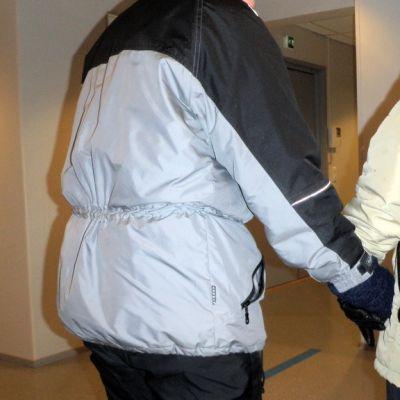 Nainen auttaa iäkästä miestä.