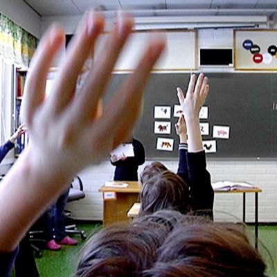 Lapset viittaavat oppitunnilla alakoulussa.