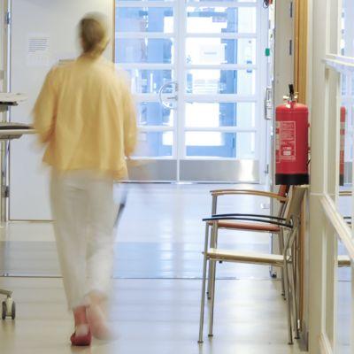 Sairaalatyöntekijä kävelee käytävällä.