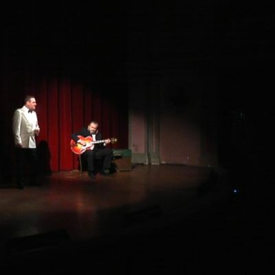 mies esittää Olavi Virtaa teatterin lavalla.