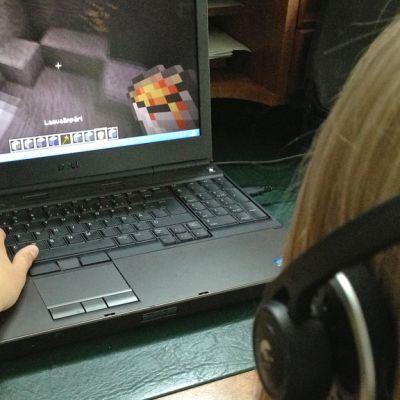 Kuvassa lapsi pelaa tieokonepeliä kuulokkeet korvillaan