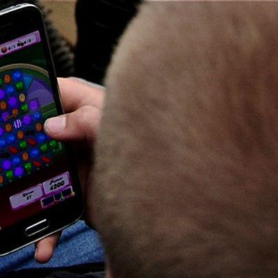 Koululainen pelaa kännykkäpeliä.