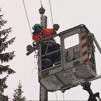 Sähköasentaja nosturin korissa korjaamassa sähkökatkoa.