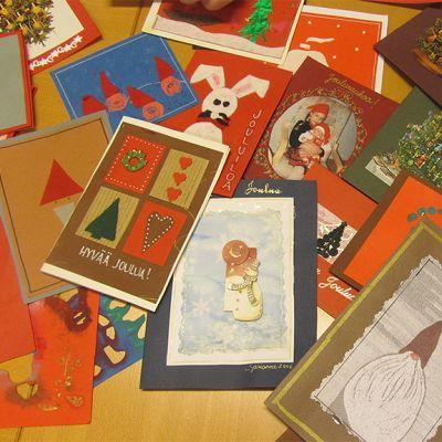 Sari Pokelan askartelemia joulukortteja pöydällä, aiheina muun muassa enkeleitä, tonttuja ja  pupuja.