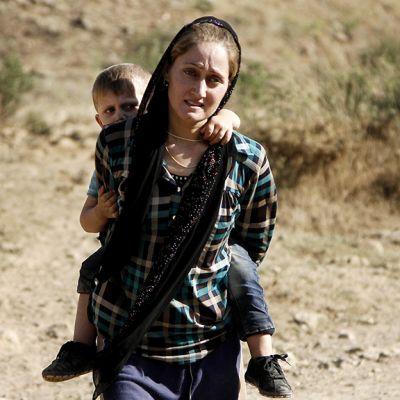 Jesidi äiti pakenee lapsensa kanssa Sinjarin kaupungista.