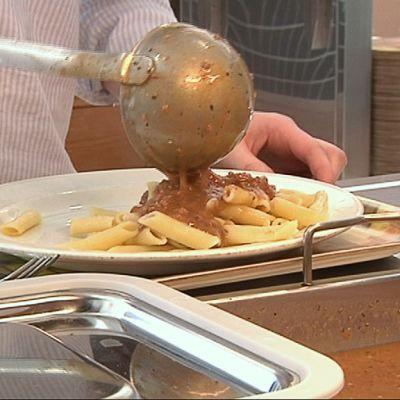 Kuvassa ruokaa laitetaan lautaselle kouluruokalassa