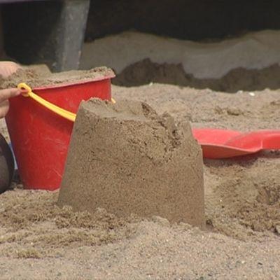 Lapsen kädet pitelevät hiekkaämpäriä hiekkalaatikolla.