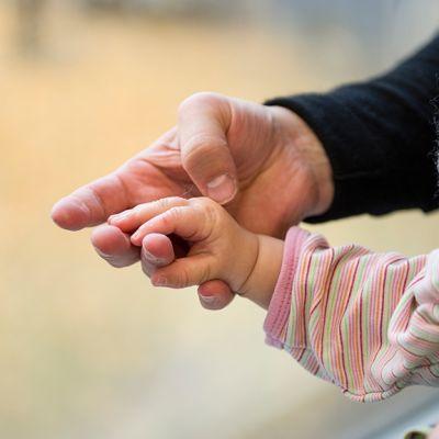 Äiti pitelee lapsen kättä.