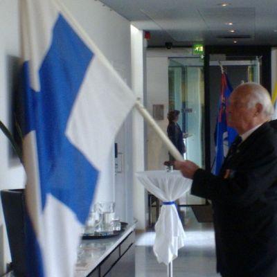 Sotaveteraani Kurt Antskog kantoi Suomen lippua Tukholman suurlähetystössä.