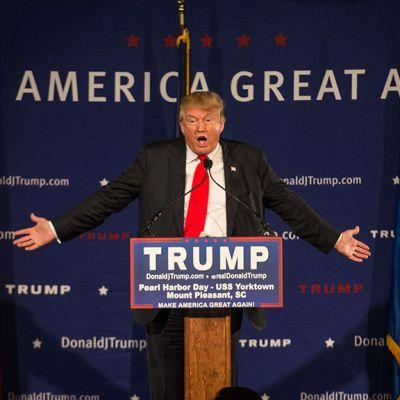Donald Trump kädet levällään puhujankorokkeella.