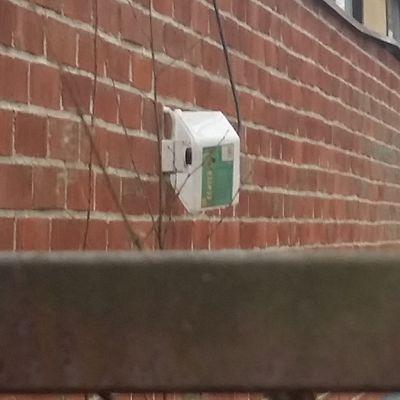 Seinällä oleva pistoke, jonka päällä suojana on muovilaatikko