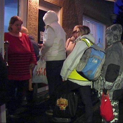 Ihmisiä seisomassa ulkona hämärässä portailla