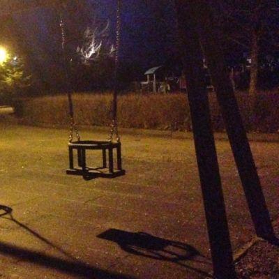 Kaksi tyhjää keinua valaistulla leikkipuistolla.