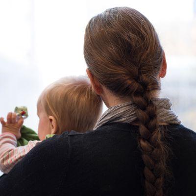 Äiti lapsi sylissä katselee ikkunasta ulos.