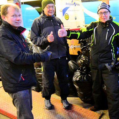 Kolme miestä näyttää peukkua lahjoituksia täynnä olevien säkkien edessä.