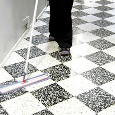 Nainen siivoaa käytävän lattiaa.