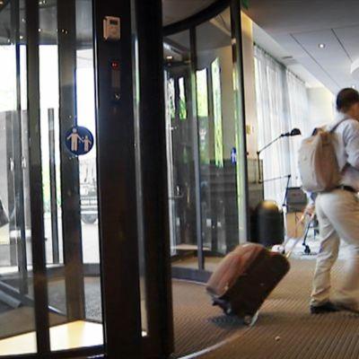 Turistit saapumassa hotellin aulaan Helsingissä.