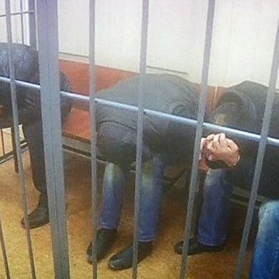 Kolme Boris Nemtsovin murhasta epäiltyä miestä kaltereiden takana kasvonsa peittäen.