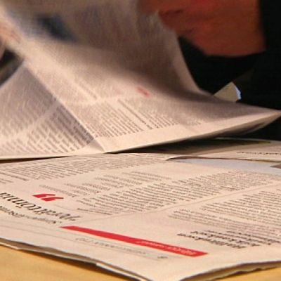 Henkilö kääntää sanomalehden sivua