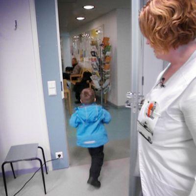 Pieni poika kävelee ulos lääkärin vastaanotolta.
