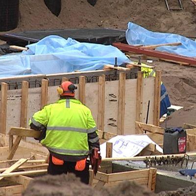 Rakennusmies kantaa lautaa työmaalla