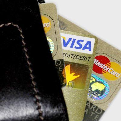 Kuvassa lompakko, joka pursuaa luottokortteja.
