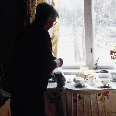 Vanhus kattaa kahvipöytää.