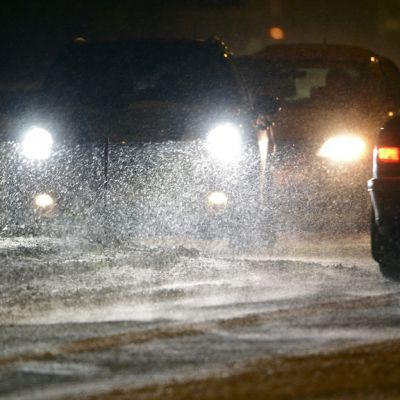 Autoja lumisateessa tiellä.